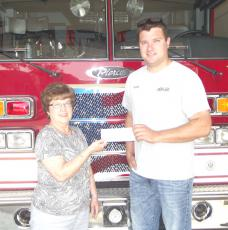 Barb Kobs (left), member of the Operation Round-Up Board at Goodhue County Cooperative Electric Association, presents a check for $1,000 to Brandon Herzig of the Lake City Fire Department.